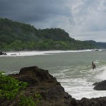 A local surfer rides a big wave on a rare day into Montezuma from the point.